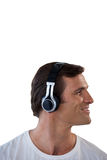 Smiling mature man listening music through headphones. Against white background Royalty Free Stock Photography