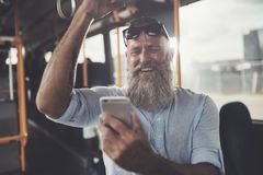 Mature man laughing while riding a bus listening to music. Smiling mature man with a long beard wearing earphones laughing at a text on his cellphone while royalty free stock photo