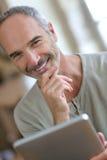 Smiling mature man looking at digital tablet Stock Photo