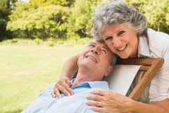 Smiling mature man lying on sun lounger. Smiling mature men lying on sun lounger and behind him his wife Stock Photo