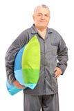 A smiling mature man in pajamas holding a pillow Stock Photos