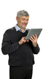 Smiling mature man with pc tablet. Senior man looking at digital tablet and smiling on white background. Pleasant communication with family via skype Stock Photos