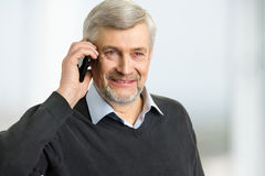 Smiling mature man with phone. Portrait of grey hair man holding phone near ear close up Royalty Free Stock Image