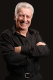 Smiling mature man. Portrait of a smiling mature man posing against black Royalty Free Stock Images