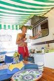Smiling mature man preparing lunch under the striped awning. Of a camper at the campsite Royalty Free Stock Photo