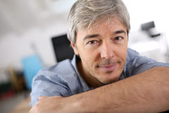 Smiling mature man relaxing at office Stock Image