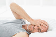 Smiling mature man resting in bed Stock Images