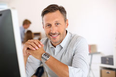 Smiling mature man sitting in office