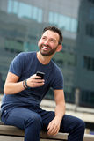 Smiling mature man sitting outdoors with smart phone Royalty Free Stock Image