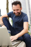 Smiling mature man sitting outdoors and working on laptop Royalty Free Stock Photography