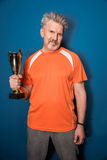 Smiling mature man in sportswear holding trophy cup. On blue Stock Photos