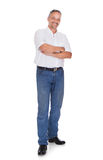 Smiling mature man standing arms crossed. Full length portrait of smiling mature man standing arms crossed over white background Royalty Free Stock Images