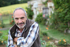 Smiling mature man standing in garden Stock Photos