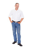 Smiling mature man standing with hands in pockets. Full length portrait of smiling mature man standing with hands in pockets over white background Stock Photos
