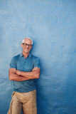Smiling mature man standing with his arms crossed Stock Photography