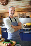 Smiling mature man standing in kitchen Stock Images