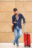 Smiling mature man with suitcase and mobile phone. Full length portrait of smiling mature man standing with suitcase and using mobile phone Stock Photo