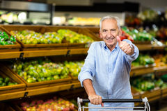 Smiling mature man with thumbs up holding cart Royalty Free Stock Photos
