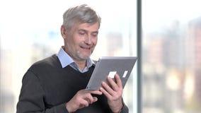 Smiling mature man using digital tablet. Handsome senior man talking via internet using computer tablet on blurred background stock footage
