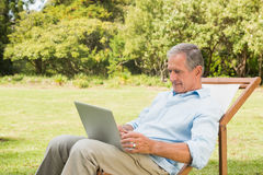 Smiling mature man using his laptop Stock Image