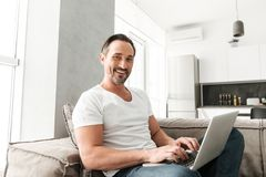 Smiling mature man using laptop computer. While sitting on a sofa at home Royalty Free Stock Images