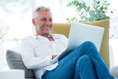 Smiling mature man using laptop. While sitting at home Royalty Free Stock Photos