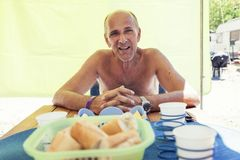 Smiling mature man while waiting for his wife for lunch. Under the striped tent of a camper at the campsite Royalty Free Stock Images