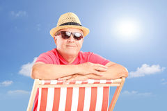 Smiling mature man wearing hat and sunglasses, posing on a beach. Chair on a sunny day Stock Image