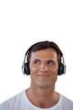 Smiling mature man wearing headphones looking away. Against white background Stock Photo