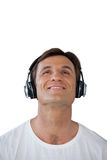 Smiling mature man wearing headphones looking up. Against white background Royalty Free Stock Photo