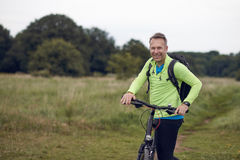 Smiling mature man wearing sportswear on bicycle. Tour through meadow royalty free stock photo