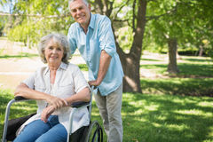 Smiling mature man with woman sitting in wheel chair at park Stock Image