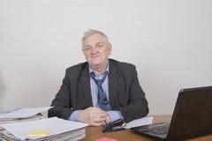 Smiling mature man at work. Sitting at a desk Royalty Free Stock Photo