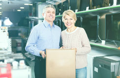 Smiling mature married couple in shop packed household appliance Stock Photo