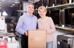 Smiling mature married couple in shop packed household appliance Stock Photos