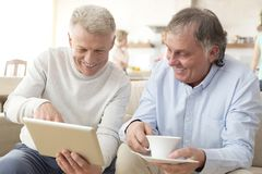Smiling mature men using digital tablet while sitting on sofa at home royalty free stock image