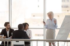 Smiling mature mentor give flipchart presentation to employees. Smiling mature businesswoman give flipchart presentation in office, talking with diverse interns stock photo