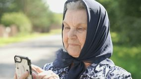 Smiling mature old woman shows smartphone outdoors stock video footage