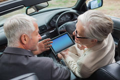 Smiling mature partners working together on tablet in classy car Royalty Free Stock Images