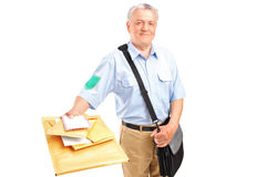 A smiling mature postman delivering letters. Isolated against white background royalty free stock images