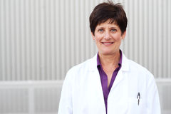 Smiling mature professional woman in labcoat. Smiling mature professional woman dressed in labcoat standing outside Stock Image