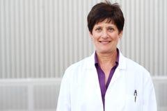 Smiling mature professional woman in labcoat Stock Image
