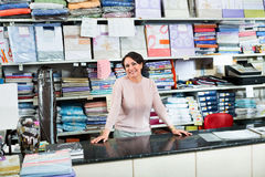 Smiling mature saleswoman offers  goods Stock Photos