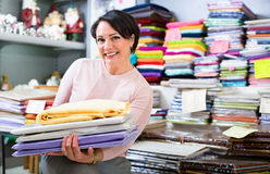 Smiling mature saleswoman offers  goods Royalty Free Stock Photography