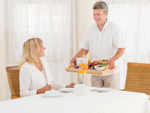 Smiling mature senior husband serving his wife healthy breakfast. Smiling middle-aged matured senior husband serving his wife healthy breakfast as she sits at Royalty Free Stock Image