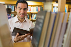 Smiling mature student with book by shelf in library Stock Photos