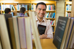 Smiling mature student holding book by shelf with men at library Royalty Free Stock Photos