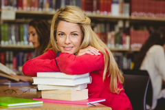 Smiling mature student leaning on a stack of books Royalty Free Stock Photos