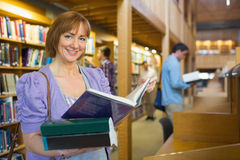 Smiling mature student with men in the background at library Stock Photos