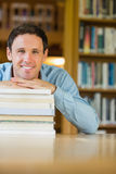 Smiling mature student with stack of books at library desk Stock Photography